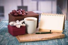 Aún vida festiva con los regalos, una taza, un cuaderno con una pluma Fotografía de archivo