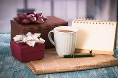 Aún vida festiva con los regalos, una taza, un cuaderno con una pluma Fotografía de archivo libre de regalías