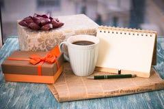 Aún vida festiva con regalos, una taza, un cuaderno y una pluma Imágenes de archivo libres de regalías