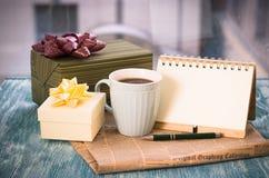 Aún vida festiva con regalos, una taza, un cuaderno y una pluma Fotos de archivo libres de regalías