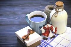 Aún vida festiva con una botella, una taza, una caja, un muñeco de nieve Fotos de archivo libres de regalías