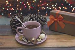 Aún vida festiva con una taza de té, de caja de regalo, de pinecones y de luces de hadas Imágenes de archivo libres de regalías