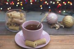 Aún vida festiva con una taza de té, cuenco de galletas, bolas del árbol de navidad Imagen de archivo libre de regalías