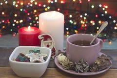 Aún vida festiva con una taza de té, el cuenco de caramelos y las velas ardientes Fotos de archivo