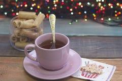 Aún vida festiva con una taza de té, el cuenco de galletas, adornó la servilleta Foto de archivo