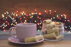 Aún vida festiva con una taza de té, un bol de vidrio de las galletas, bolas del árbol de navidad Fotografía de archivo libre de regalías