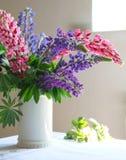 Aún-vida, florero blanco con lupine púrpura y rosado en la tabla, Foto de archivo libre de regalías
