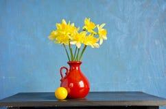 Narciso de la primavera en florero rojo y bola amarilla Imagenes de archivo