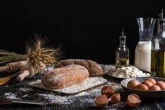 Aún vida hermosa con los diferentes tipos de pan, de grano, de harina en peso, de oídos del trigo, de jarra de leche y de huevos Fotos de archivo