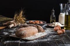 Aún vida hermosa con los diferentes tipos de pan, de grano, de harina en peso, de oídos del trigo, de jarra de leche y de huevos Foto de archivo libre de regalías