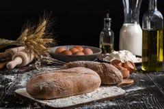 Aún vida hermosa con los diferentes tipos de pan, de grano, de harina en peso, de oídos del trigo, de jarra de leche y de huevos Imagen de archivo