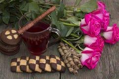 Aún vida hermosa de rosas, de las galletas y del té en una tabla de madera Fotografía de archivo