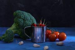 Aún vida hermosa en un oscuro Bróculi, ajo y tomates Pimienta de chile en un pequeño cubo luz inusual Fotos de archivo libres de regalías