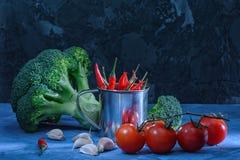 Aún vida hermosa en un oscuro Bróculi, ajo y tomates rojos Pimienta de chile en un pequeño cubo luz inusual Fotos de archivo libres de regalías