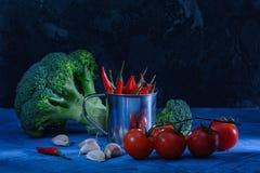 Aún vida hermosa en un oscuro Bróculi, ajo y tomates rojos Pimienta de chile en un pequeño cubo luz inusual Fotografía de archivo libre de regalías