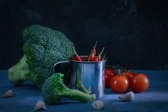 Aún vida hermosa en un oscuro Bróculi y tomates Pimienta de chile en un pequeño cubo luz inusual Foto de archivo libre de regalías