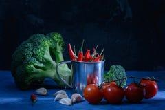Aún vida hermosa en una luz oscura, inusual Bróculi, ajo y tomates rojos Pimienta de chile en un pequeño cubo Imágenes de archivo libres de regalías