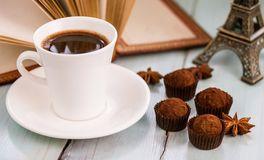Aún vida hermosa: trufas de chocolate, canela, una taza de café y un libro abierto Imagen de archivo libre de regalías