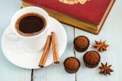 Aún vida hermosa: trufas de chocolate, canela, una taza de café y un libro abierto Fotografía de archivo libre de regalías