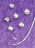 Aún vida jewlelry de plata con el fondo púrpura Fotografía de archivo