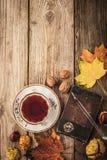 Aún vida otoñal con el regalo de la naturaleza, el cuaderno del vintage y el té con la película filtran el fondo del efecto Fotografía de archivo