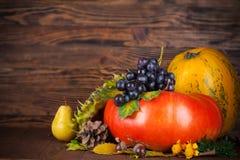 Aún vida otoñal con la calabaza y las uvas en el tablero de madera Fotografía de archivo libre de regalías