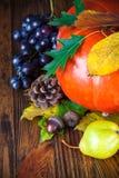 Aún vida otoñal con la calabaza y las uvas en el tablero de madera Foto de archivo