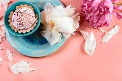 Aún vida pintoresca en tonos rosados, la placa decorativa con la torta cremosa rodeada por los piones blancos de los pétalos, cer Imagen de archivo libre de regalías