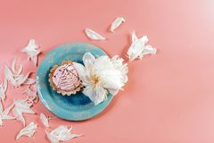 Aún vida pintoresca en tonos rosados, placa decorativa con la torta cremosa rodeada por los piones blancos de los pétalos, en un  Foto de archivo