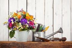 Aún-vida que cultiva un huerto rústica con el ramo de la flor Imagenes de archivo