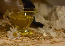 Aún vida rústica con aceite de oliva en una taza de cristal, el campo florece, los granos de avena Foto de archivo libre de regalías