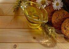 Aún vida rústica con aceite de oliva en una taza de cristal, flores del campo y espiguillas del trigo Fotos de archivo libres de regalías