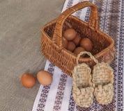 Aún vida rústica con la cesta con los huevos y los zapatos de la estopa Fotos de archivo libres de regalías