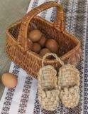 Aún vida rústica con la cesta con los huevos y los zapatos de la estopa Foto de archivo