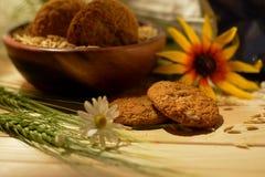 Aún vida rústica con las galletas de harina de avena, los granos de avena y los wildflowers Fotografía de archivo libre de regalías