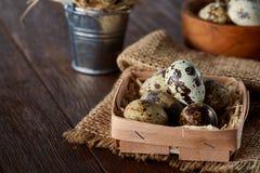 Aún vida rústica con los huevos de codornices en cubo, caja y cuenco en una servilleta de lino sobre el fondo de madera, foco sel Imágenes de archivo libres de regalías