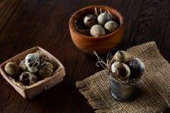 Aún vida rústica con los huevos de codornices en cubo, caja y cuenco en una servilleta de lino sobre el fondo de madera, foco sel Imagenes de archivo
