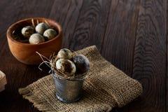Aún vida rústica con los huevos de codornices en cubo, caja y cuenco en una servilleta de lino sobre el fondo de madera, foco sel Fotografía de archivo libre de regalías