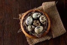 Aún vida rústica con los huevos de codornices en cubo, caja y cuenco en una servilleta de lino sobre el fondo de madera, foco sel Foto de archivo