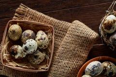 Aún vida rústica con los huevos de codornices en cubo, caja y cuenco en una servilleta de lino sobre el fondo de madera, foco sel Imagen de archivo libre de regalías