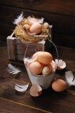 Aún vida rústica con los huevos en el cubo de madera del vintage para pascua Fotografía de archivo