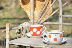 Aún vida rústica con tazas de sombrero del té y de paja Imagen de archivo