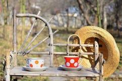 Aún vida rústica con tazas de sombrero del té y de paja Foto de archivo libre de regalías