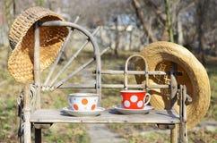Aún vida rústica con tazas de sombreros del té y de paja Imagenes de archivo