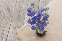 Aún vida rústica con un ramo de flores azules en un CCB de madera Fotos de archivo