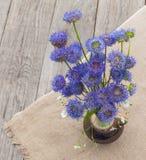 Aún vida rústica con un ramo de flores azules en un CCB de madera Foto de archivo libre de regalías