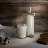 Aún vida rústica con una botella de leche, de huevos y de pan en fondo de la pared de madera áspera Fotografía de archivo libre de regalías