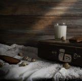 Aún vida rústica con una maleta vieja, un vidrio de leche y huevos en un fondo de una pared de madera áspera Imagen de archivo libre de regalías