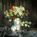 Aún vida rústica Flores y amapolas de la manzanilla del ramo en una poder del metal Imágenes de archivo libres de regalías