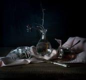 Aún vida rústica la ramita seca en un florero de cristal, rosa cubre y los tarros en una tabla de madera Fondo negro Fotos de archivo libres de regalías